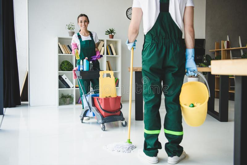 Cropped shot of young cleaners holding various cleaning equipment. In office royalty free stock image