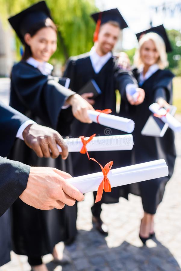 cropped shot of young graduated students holding stock photography
