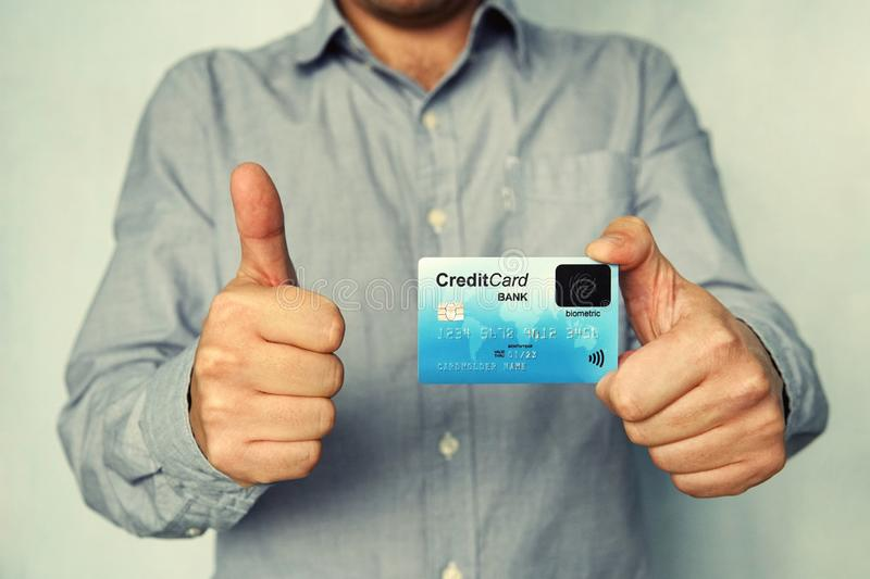 Cropped shot of young man in shirt holding credit card with biometric technology and showing thumb up. Man is glad to use bank royalty free stock images