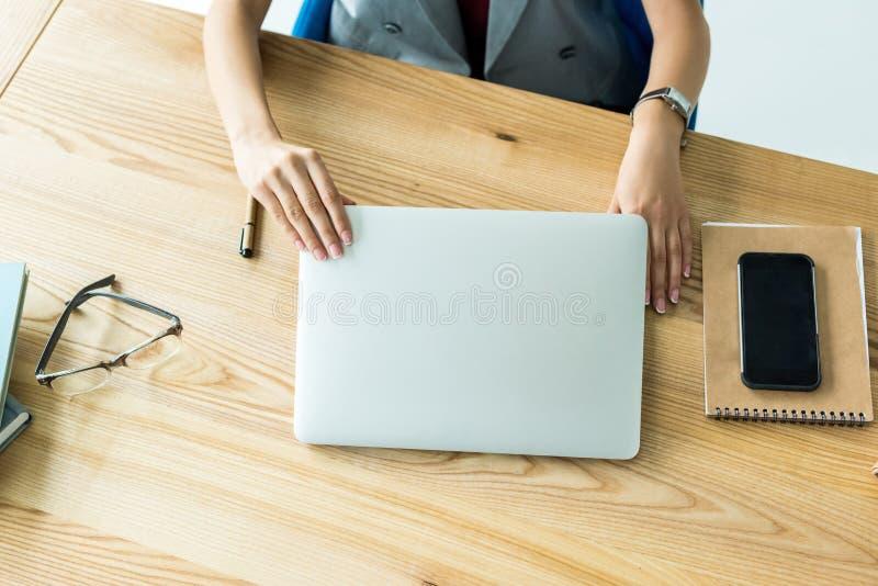 cropped strzał bizneswomanu obsiadanie przy miejscem pracy z notatnikiem obrazy stock
