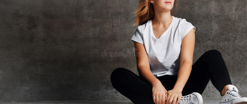 Cropped strzał dziewczyna siedzi na podłogowy pobliskim w cajgach siwieje ścianę zdjęcia royalty free