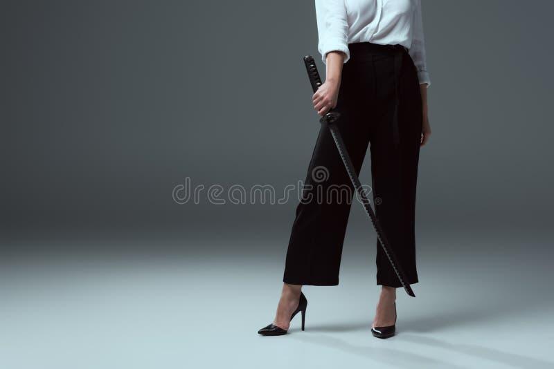 cropped strzał dziewczyna trzyma katana kordzika w wysokości heeled buty zdjęcie royalty free