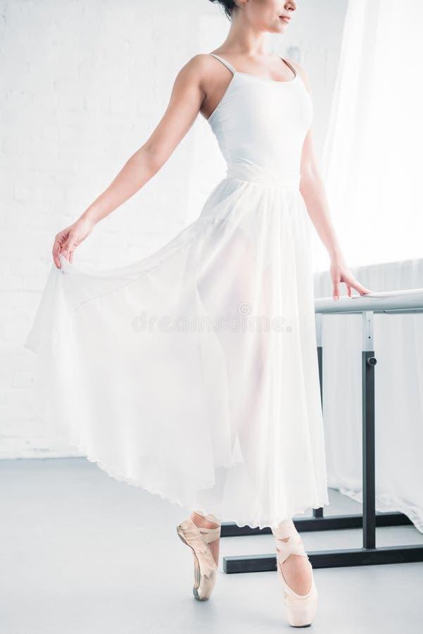 cropped strzał elegancka młoda balerina w bielu smokingowym ćwiczy balecie zdjęcie stock