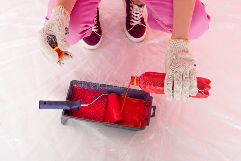 cropped strzał kobieta nalewa czerwoną farbę od butelki w rolkową tacę w ochronnych rękawiczkach obraz royalty free