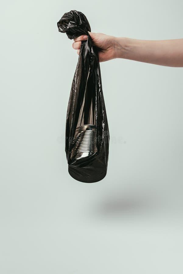 cropped strzał kobiety mienia torba na śmiecie z puszką odizolowywającą na popielatym obrazy stock