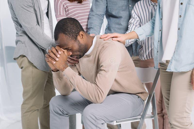 cropped strzał ludzie wspiera przygnębionego w średnim wieku amerykanina afrykańskiego pochodzenia mężczyzna zdjęcie stock