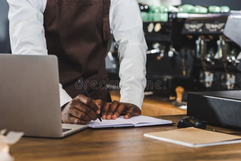 cropped strzał młody amerykanina afrykańskiego pochodzenia barista bierze notatki i używa laptop obrazy royalty free