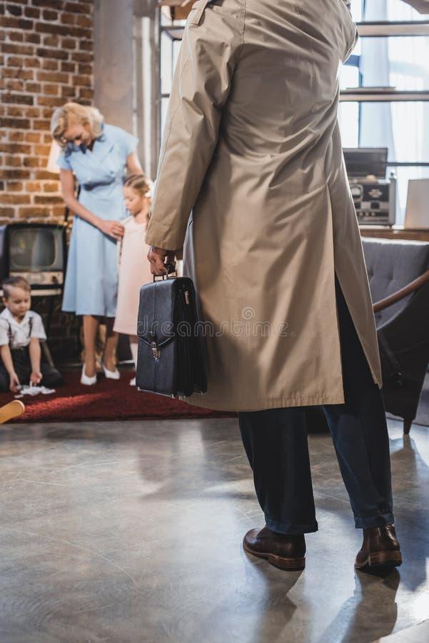 cropped strzał ojciec z teczki przybycia domem podczas gdy szczęśliwa rodzina bawić się wpólnie obrazy stock