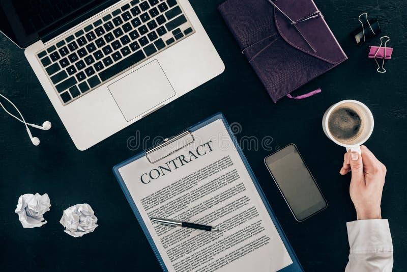 Cropped strzał pije kawę przy miejscem pracy z kontraktem bizneswoman obrazy royalty free