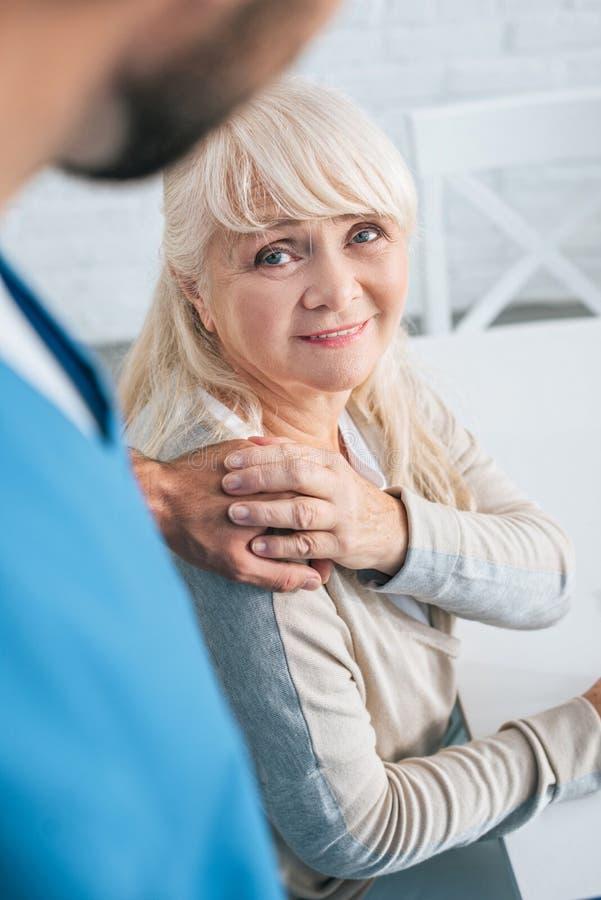 cropped strzał pracownik opieki społecznej i uśmiechnięta starsza kobieta zdjęcie stock