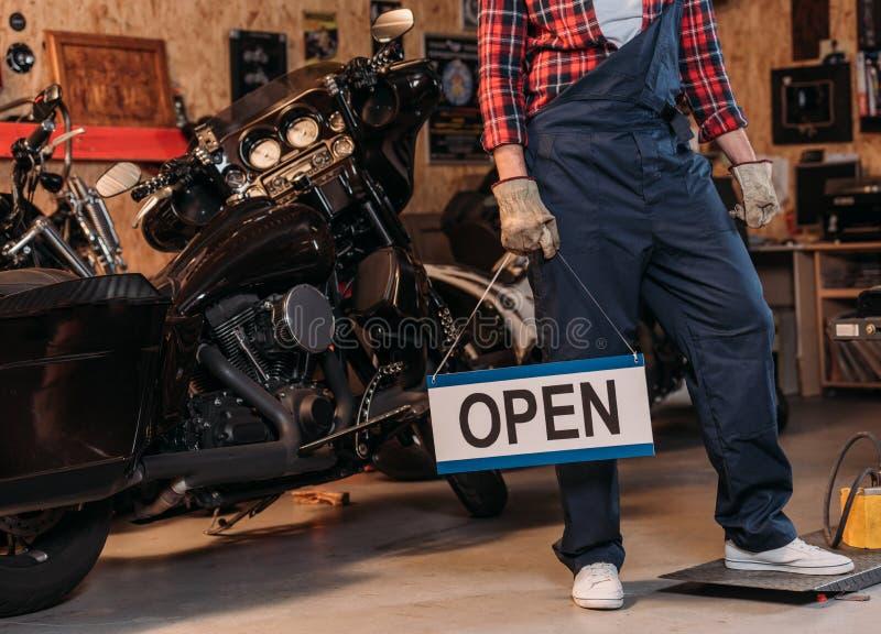 cropped strzał rower naprawy staci pracownika mienia otwarty signboard obraz stock