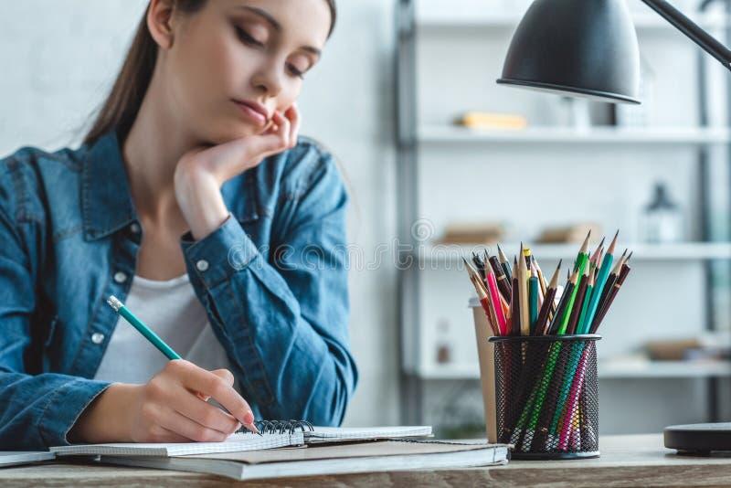 cropped strzał zanudzająca dziewczyna pisze w notatniku i studiować zdjęcia stock