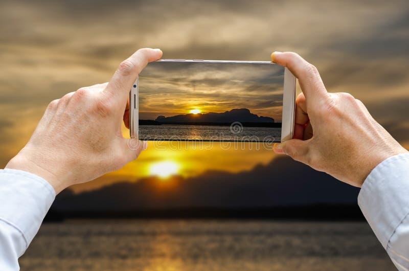 Cropped strzału widok mężczyzna ręki robi fotografii na telefon komórkowy kamerze jest wysokimi górami z iluminującymi szczytami  zdjęcie stock