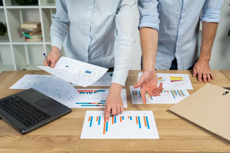 Cropped two banker economist financier person in formalwear shirt stand behind desktop table in loft interior make discuss. Demonstrate dynamic on trade blanks royalty free stock photo