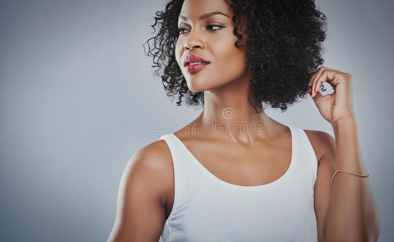 Cropped upper body view of young woman. Cropped upper body view of beautiful young African woman looking sideways with hands touching hair and copy space stock photo