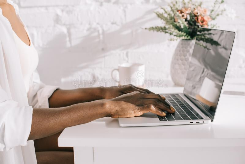 Cropped view of african american woman using laptop stock images
