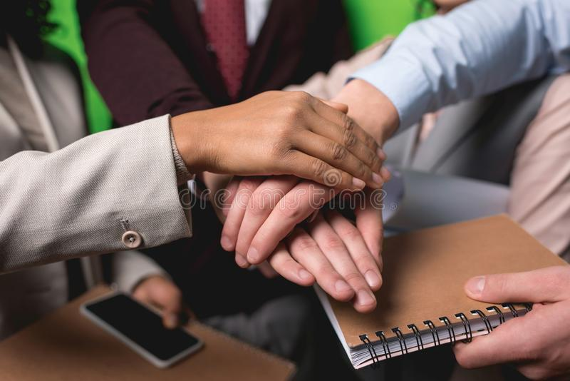 cropped view of business team holding hands together in front of stock photo