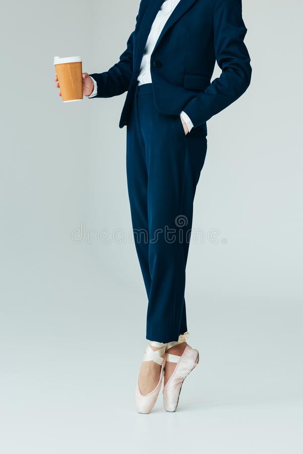 Cropped view of businesswoman in ballet shoes holding coffee to go,. Isolated on grey royalty free stock image