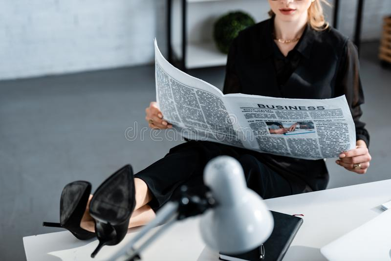 Cropped view of businesswoman in black clothes sitting at table and. Reading newspaper royalty free stock photography