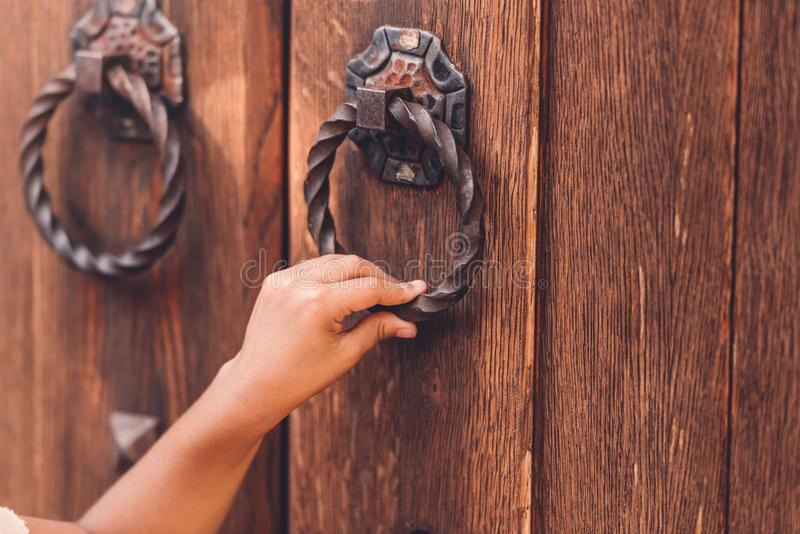 Cropped view of child knocking in door with metal handle stock images