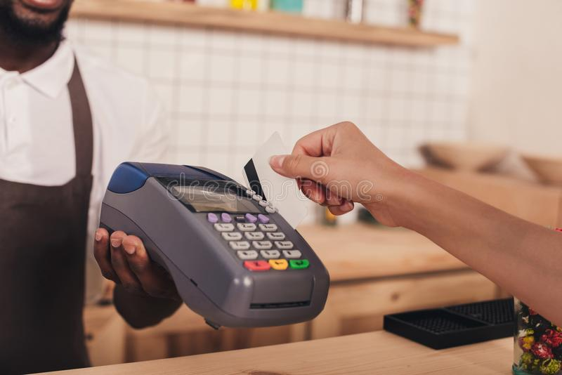 Cropped view of client paying with credit card and terminal in cafe royalty free stock image