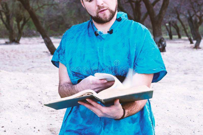 Cropped view of concentrated handsome bearded man in blue kimono sitting, leafing through large book. And reading on sandy beach near trees stock photo