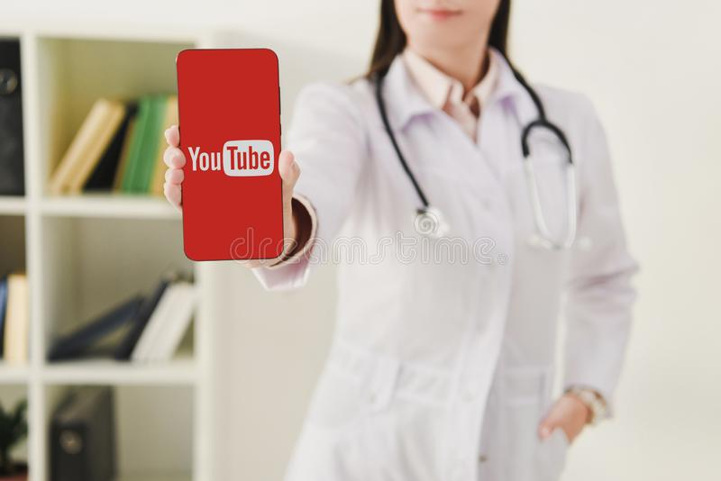 cropped view of doctor presenting smartphone stock photos