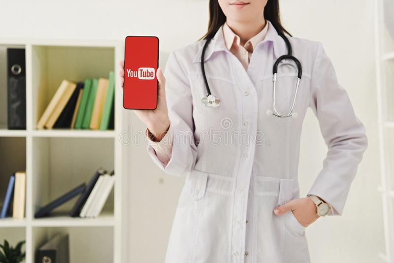 Cropped view of doctor with stethoscope showing smartphone. With youtube app stock photo