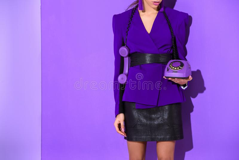 cropped view of elegant girl posing in purple jacket and holding vintage rotary phone at ultra violet wall stock photo