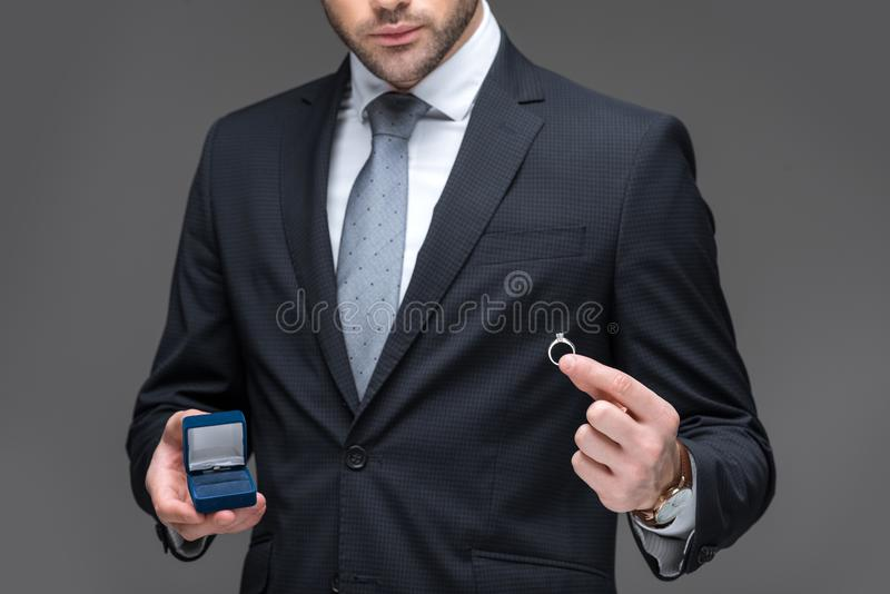 Cropped view of elegant man proposing with ring,. Isolated on grey royalty free stock images