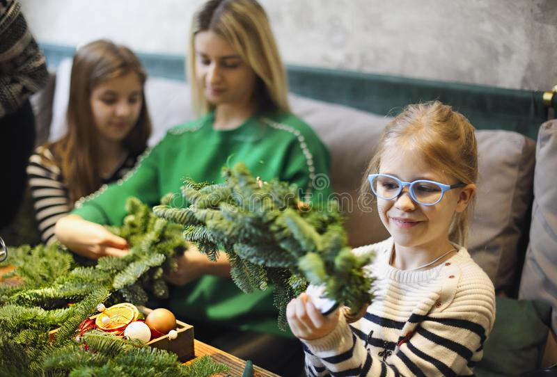 Family making christmas wreath from fir branches, christmas balls and pine cones on the wooden table royalty free stock photos