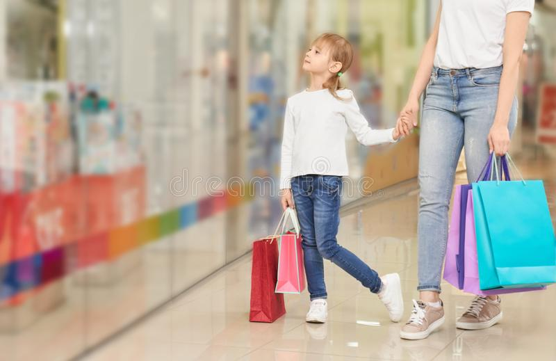 Funny girl keeping hand of mother in bag mall stock images