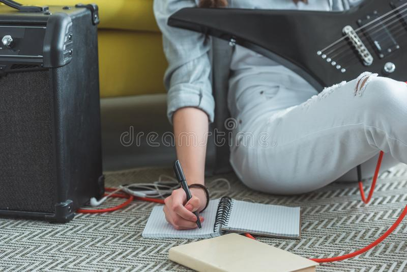 cropped view of girl with electric guitar writing song in copybook while sitting stock photos
