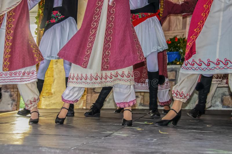 Cropped view of Greek dancers on stage in beautiful embroidered costume with women in front of men - legs and feet - movement blur stock images