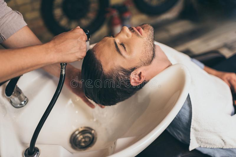Cropped view hairstylist washing clients hair in barber royalty free stock photos