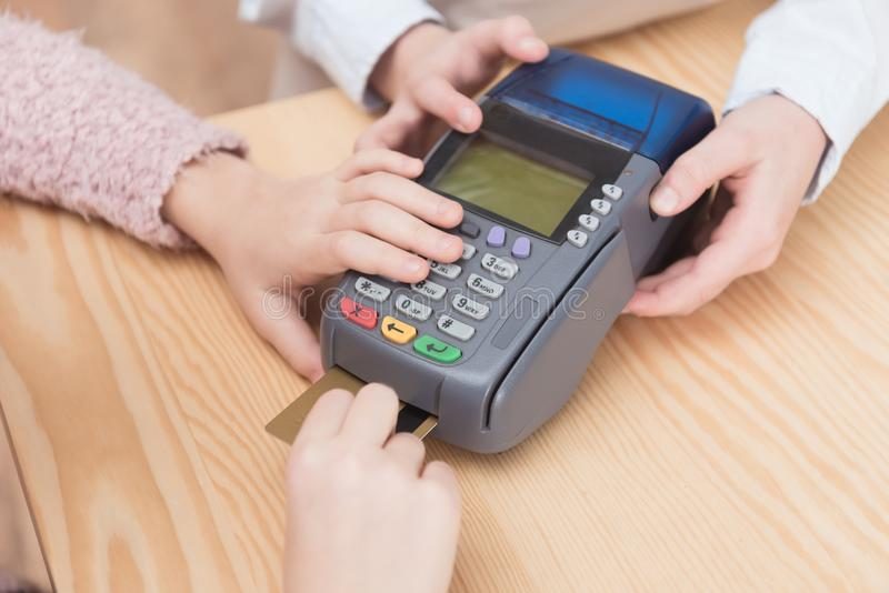 Cropped view of kid paying with credit card in payment. Terminal royalty free stock photos