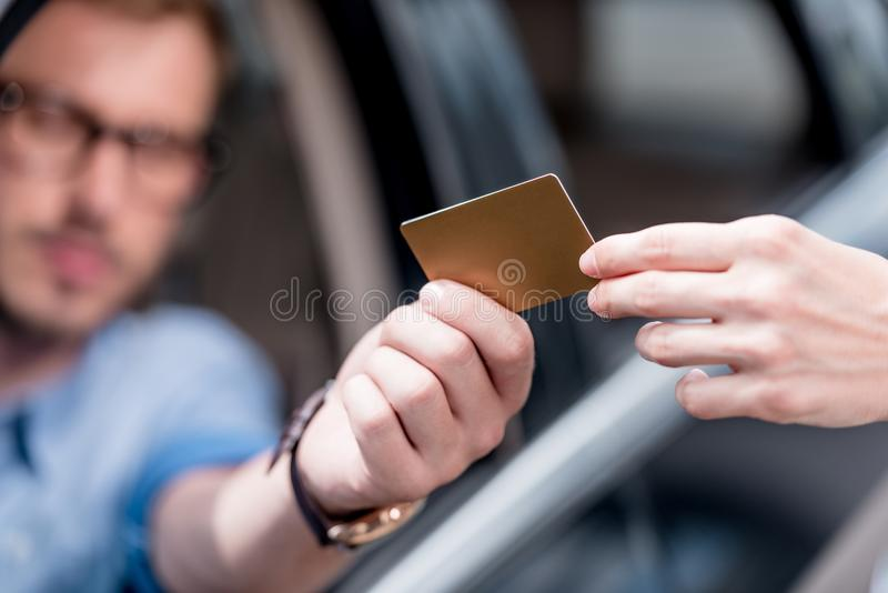Cropped view of man paying with credit card while. Driving car stock images