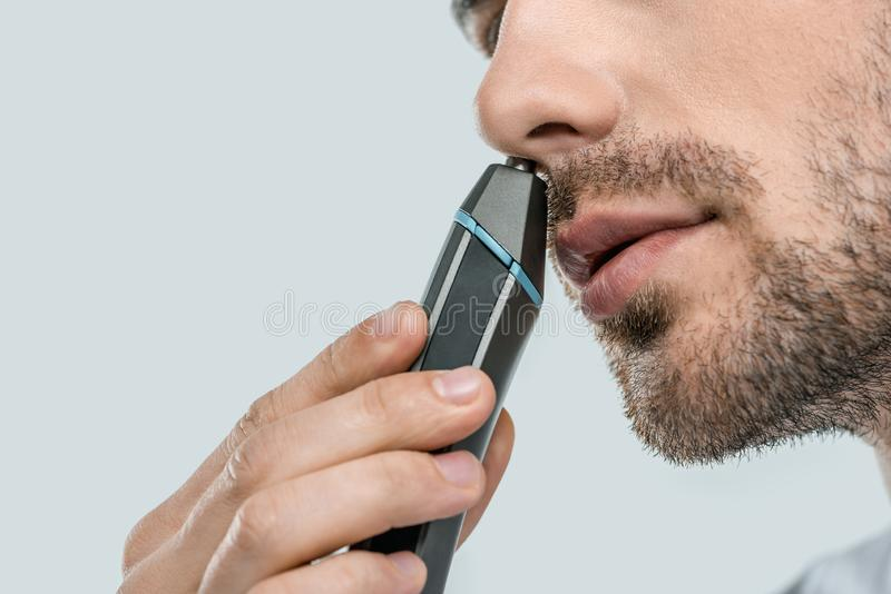 Cropped view of man using electric trimmer for nose. Isolated on grey stock images
