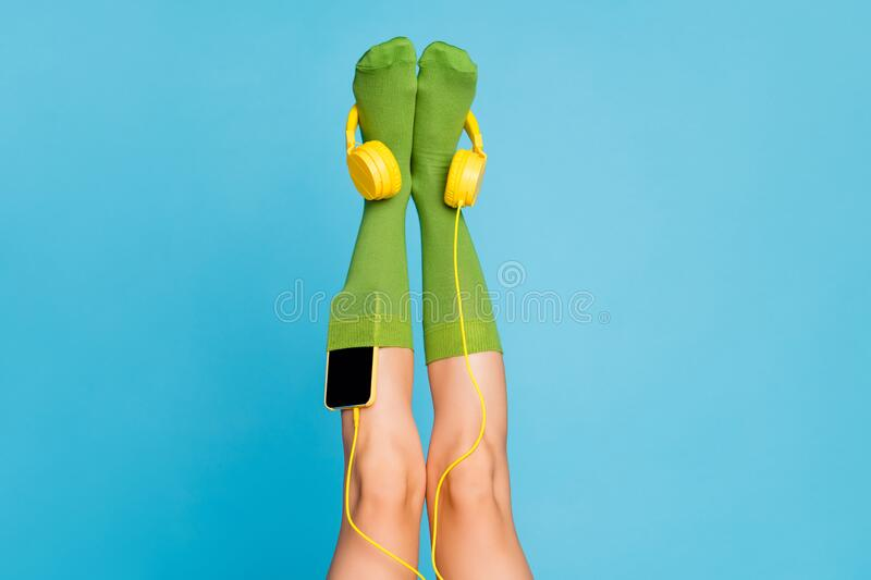 Cropped view of nice attractive lovely long legs wearing cozy comfortable mint green brandy socks with mp3 player put. Isolated over bright vivid shine vibrant stock image