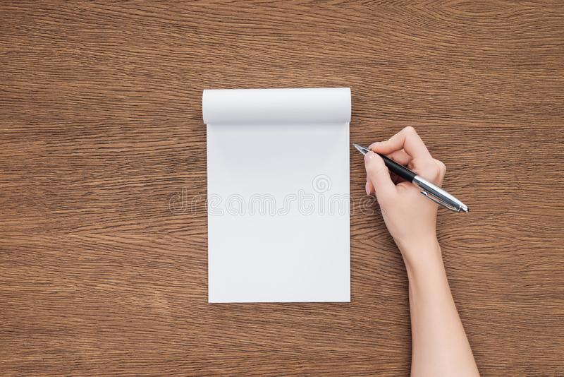 Cropped view of person holding pen over blank notebook. On wooden background stock photos