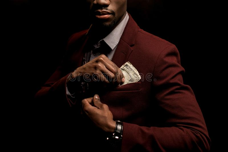 cropped view of rich african american man putting dollar banknotes into pocket stock photography