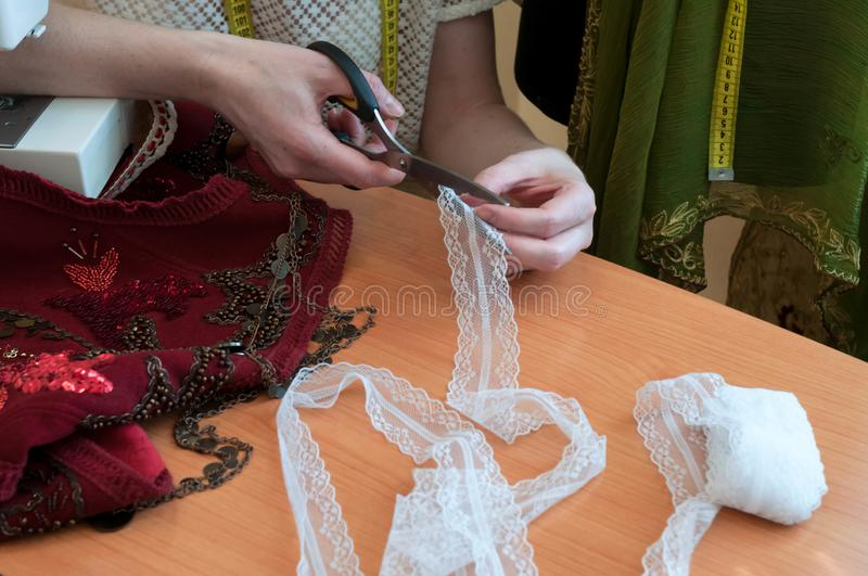 Seamstress cutting lace with scissors on wooden table near red embroidered vest. Cropped view of seamstress cutting lace with scissors on wooden table near red royalty free stock photo