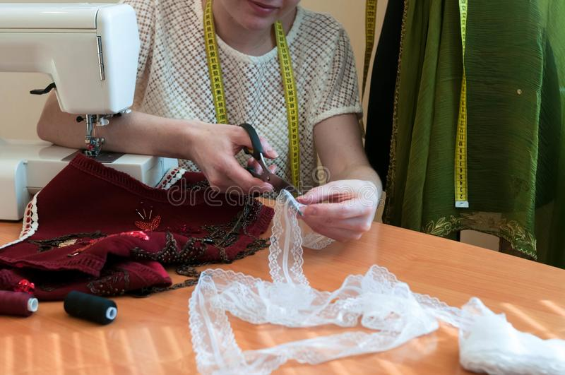 Cropped view of seamstress sitting at table with sewing machine and cutting lace royalty free stock image