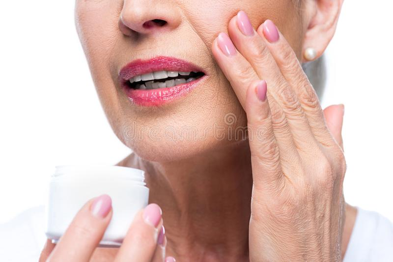 Senior woman applying face cream. Cropped view of senior woman applying anti-wrinkle face cream, isolated on white royalty free stock photos