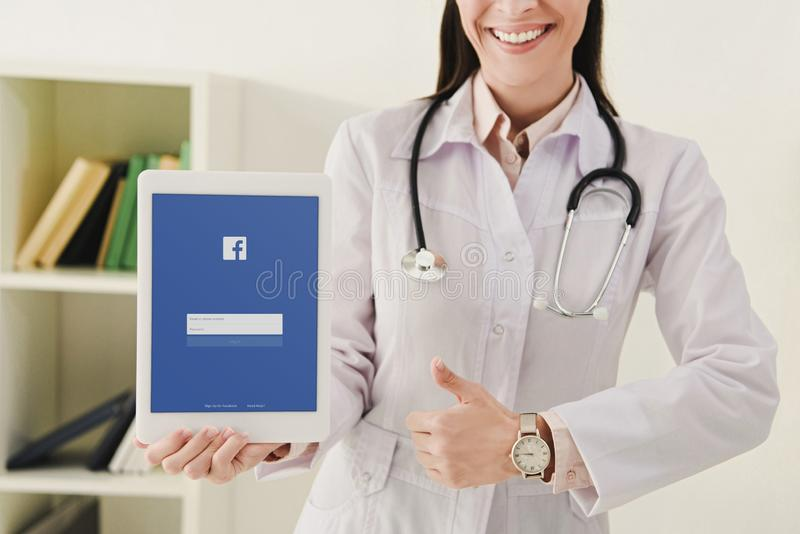 Cropped view of smiling doctor showing thumb up and presenting tablet. With facebook app stock photos