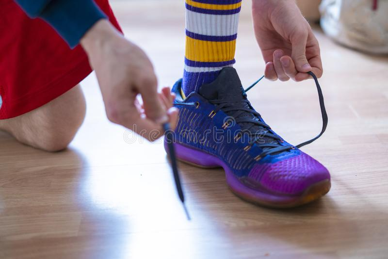 Cropped view of sportsman hands tie shoelaces of sneakers at the locker room i stock photos