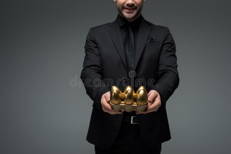 Cropped view of stylish man with golden eggs royalty free stock photos