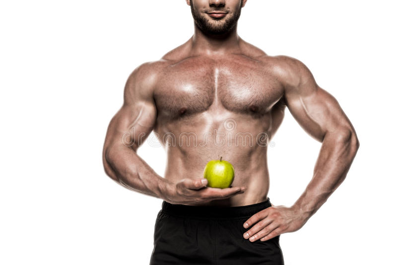 Cropped view of sweaty muscular sportsman holding green apple isolated on white stock photo