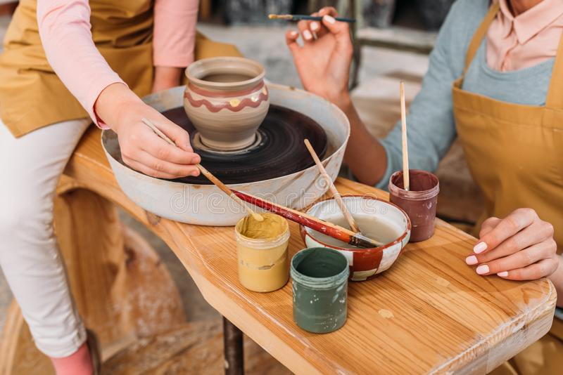 cropped view of teacher and kid painting ceramic pot with brushes royalty free stock photo
