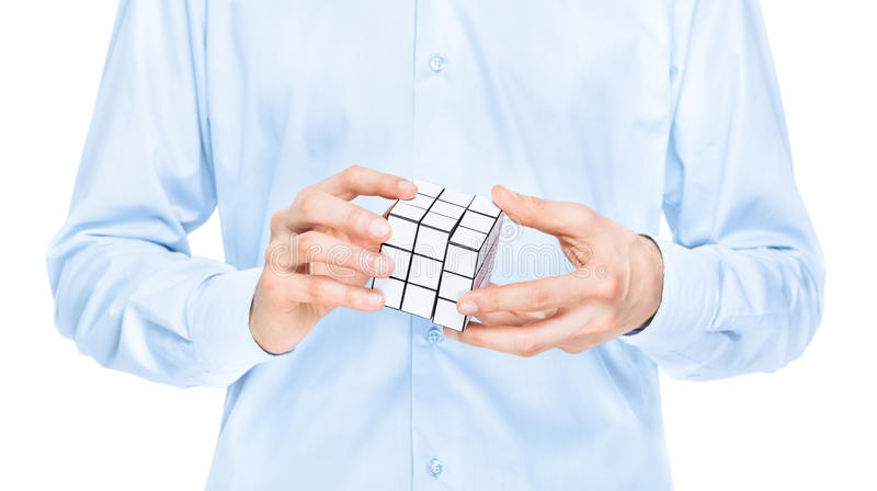 Businessman solving blank puzzle game. Cropped view of the torso and hands of a man holding a blank white cubic twist puzzle game which he is trying to solve royalty free stock image